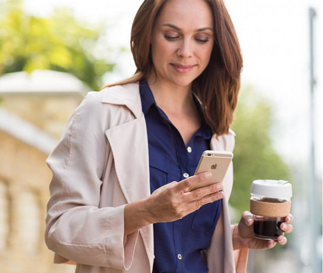 A lady and a phone and a coffee